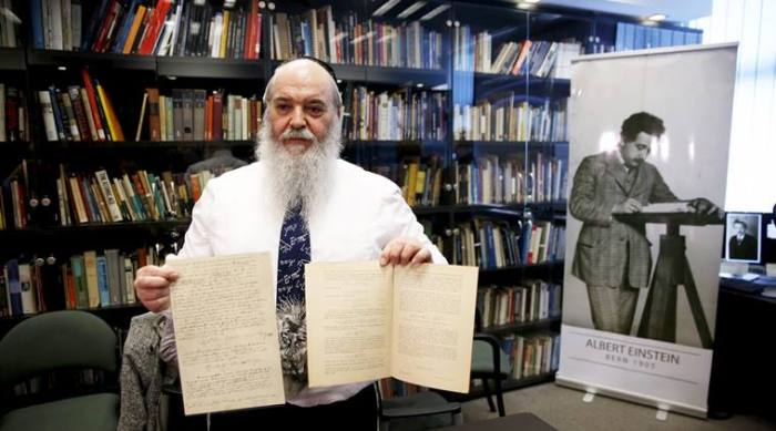 Grosz displays original documents related to Einstein's hypothesis of the existence of gravitational waves during a news conference in Jerusalem